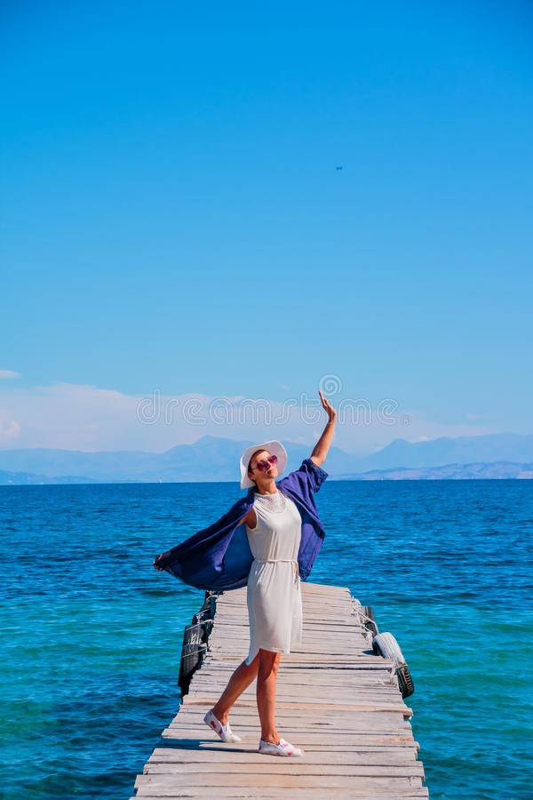 Young happy woman on the bridge near sea, summer time, happy vacation concept. Copy space. Beautiful woman in white dress stock photography
