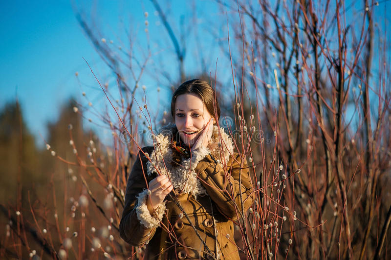 Young happy woman clothed sheepskin coat and scarf. Girl holding willow branches. Spring time. stock images