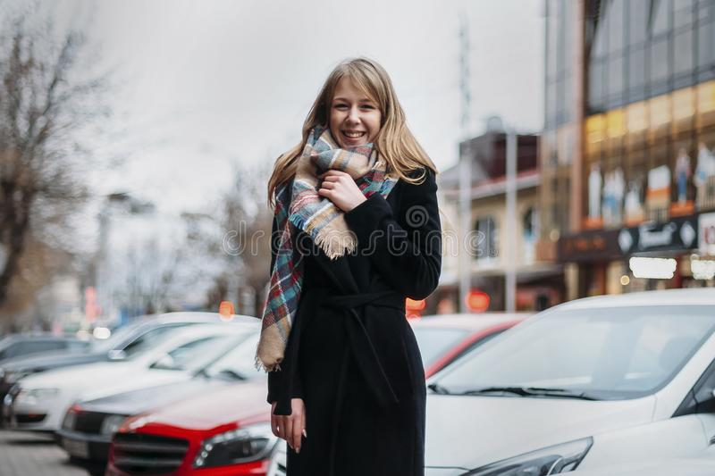Young happy woman in coat and scarf laughing. girl walking around city royalty free stock images