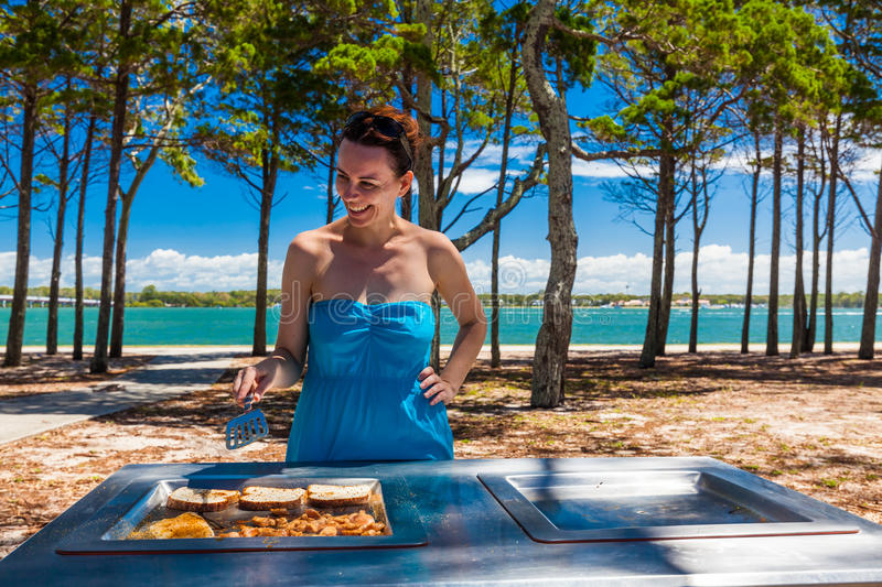 Young happy woman cooking barbeque on the beach in Australia royalty free stock photo