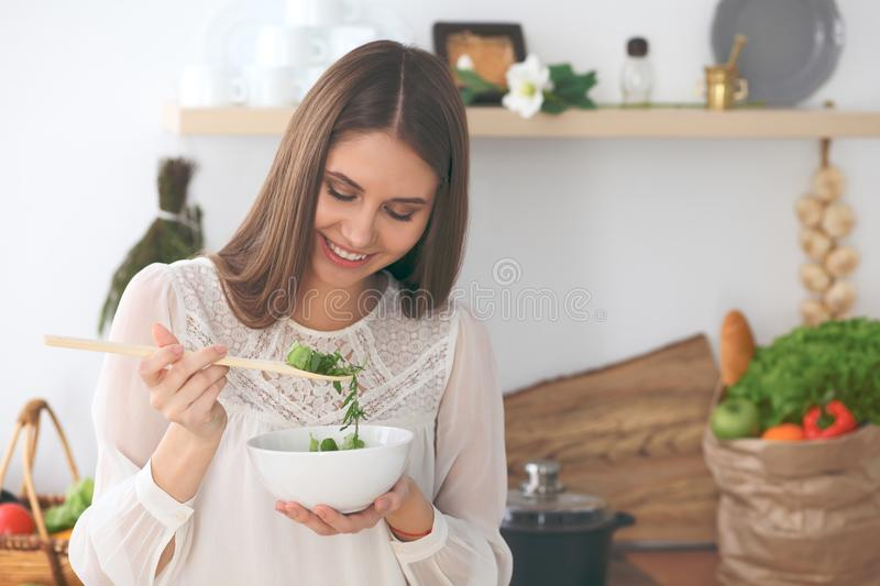 Young happy woman cooking in the kitchen. Healthy meal, lifestyle and culinary concept stock image
