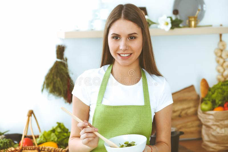 Young happy woman cooking in the kitchen. Healthy meal, lifestyle and culinary concepts. Good morning begins with fresh. Salad royalty free stock photos