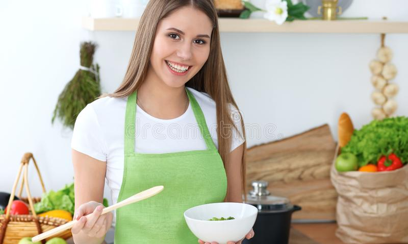 Young happy woman cooking in the kitchen. Healthy meal, lifestyle and culinary concepts. Good morning begins with fresh. Salad royalty free stock photo
