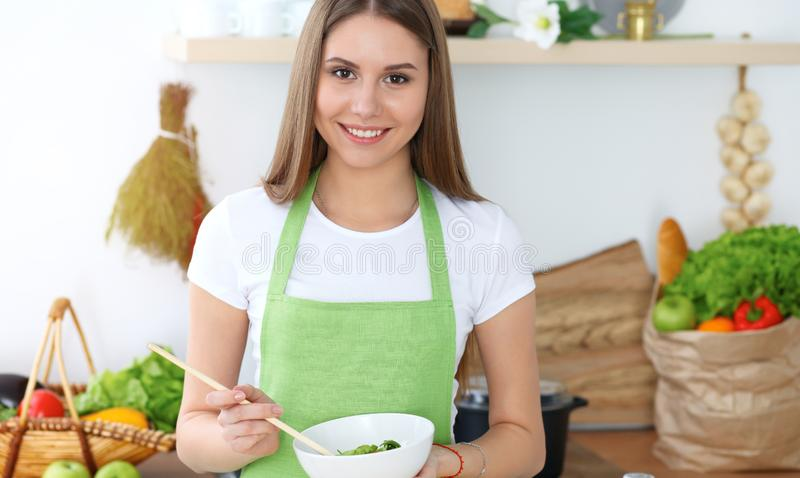 Young happy woman cooking in the kitchen. Healthy meal, lifestyle and culinary concepts. Good morning begins with fresh. Salad royalty free stock image