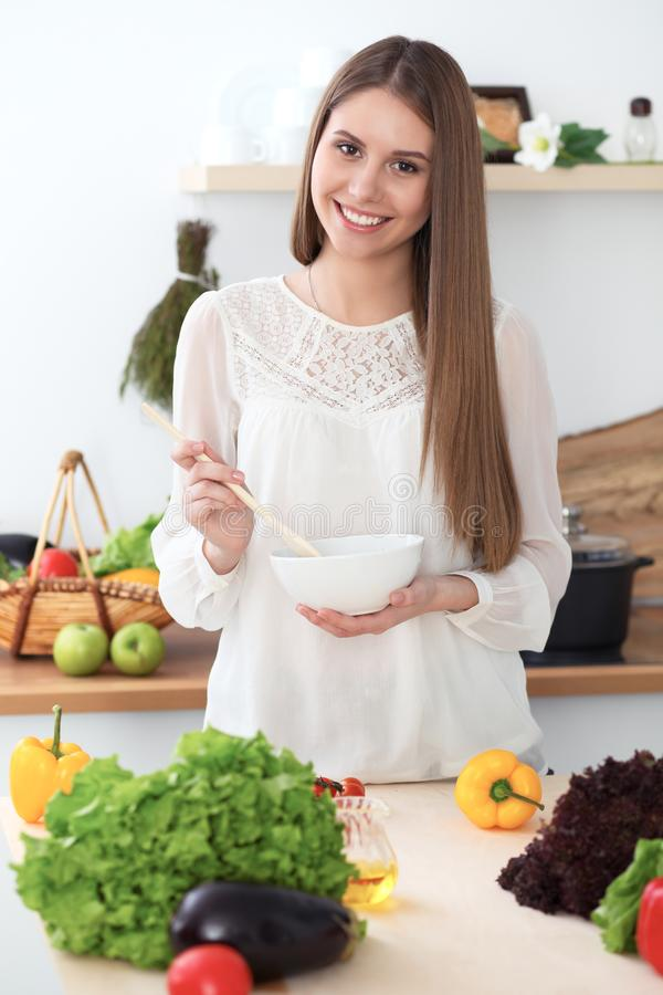 Young happy woman cooking in the kitchen. Healthy meal, lifestyle and culinary concepts. Good morning begins with fresh. Salad royalty free stock photography