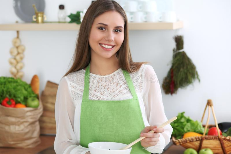 Young happy woman cooking in the kitchen. Healthy meal, lifestyle and culinary concepts. Good morning begins with fresh. Salad royalty free stock images