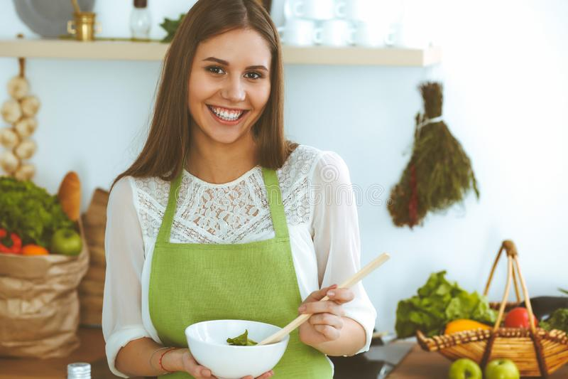 Young happy woman cooking in the kitchen. Healthy meal, lifestyle and culinary concepts. Good morning begins with fresh. Salad stock image