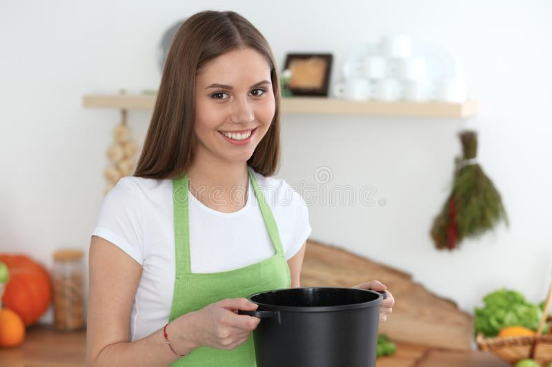 Young happy woman cooking soup in the kitchen. Healthy meal, lifestyle and culinary concept. Smiling student girl. Preparing vegetarian meal at home royalty free stock image