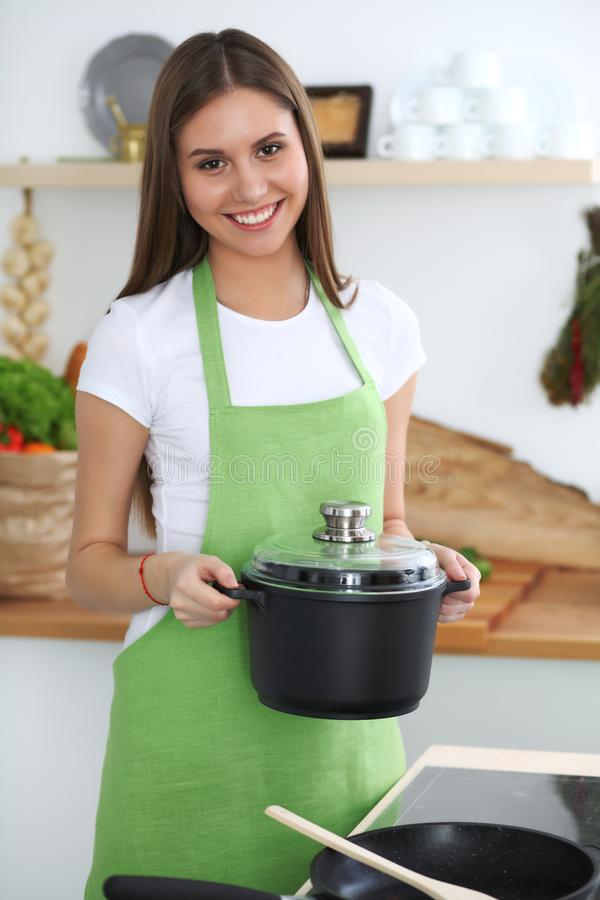 Young happy woman cooking soup in the kitchen. Healthy meal, lifestyle and culinary concept. Smiling student girl. Preparing vegetarian meal at home royalty free stock photo