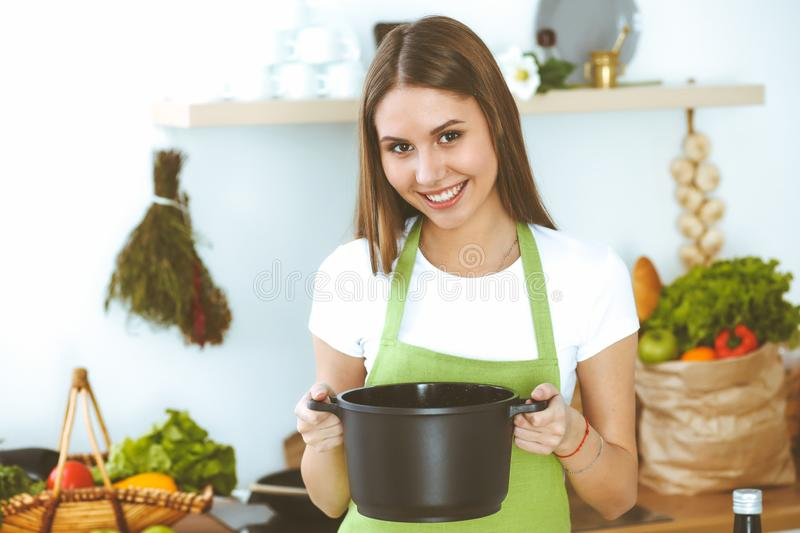 Young happy woman cooking soup in the kitchen. Healthy meal, lifestyle and culinary concept. Smiling student girl stock images