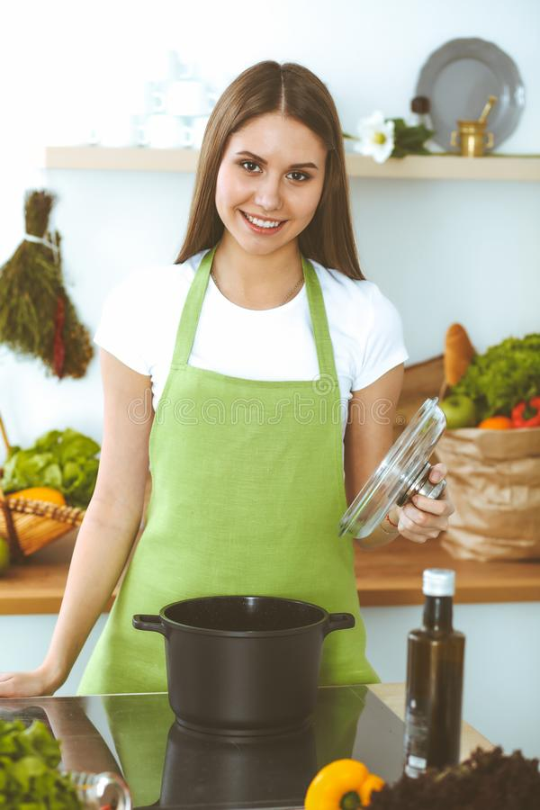 Young happy woman cooking soup in the kitchen. Healthy meal, lifestyle and culinary concept. Smiling student girl royalty free stock photos