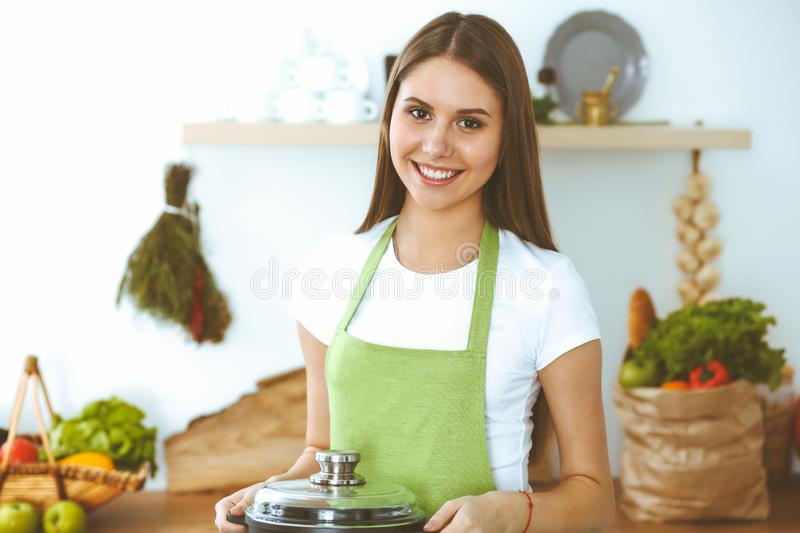 Young happy woman cooking soup in the kitchen. Healthy meal, lifestyle and culinary concept. Smiling student girl. Preparing vegetarian meal at home stock photography