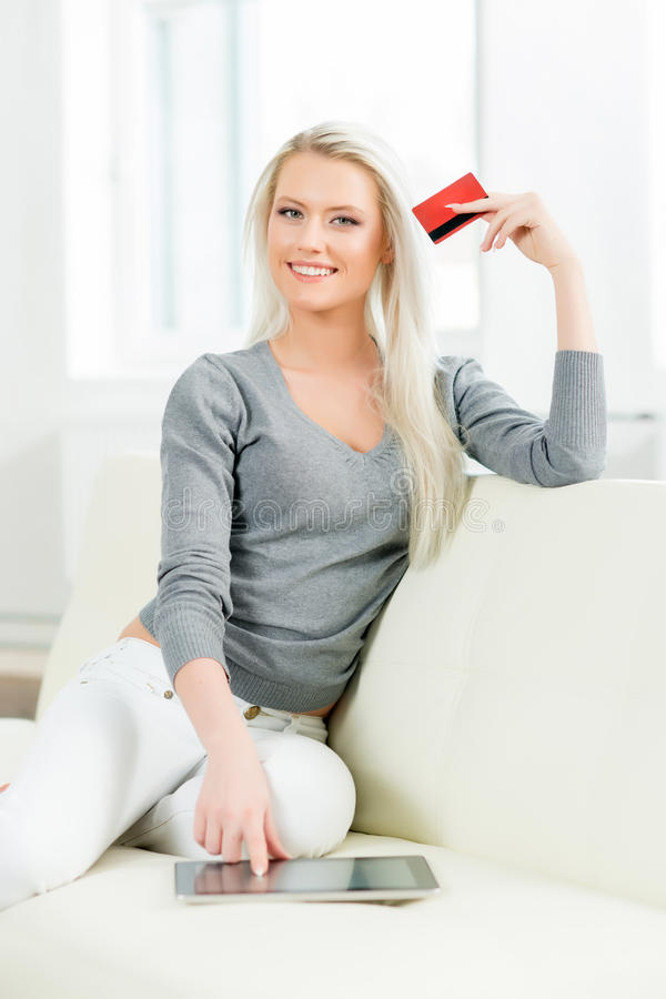 Young and happy woman with a credit card. Online shopping concept stock image