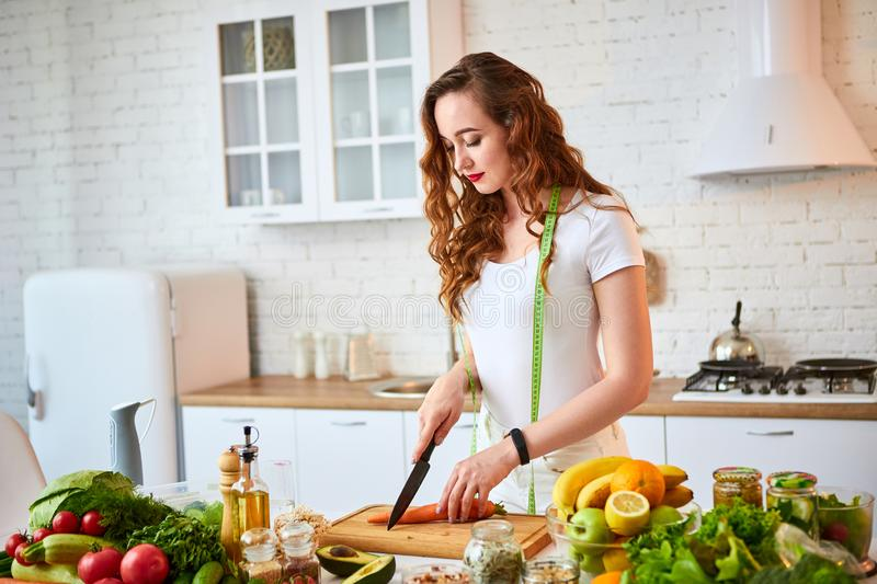 Young happy woman cutting carrot in the beautiful kitchen with green fresh ingredients indoors. Healthy food and Dieting concept. stock photos