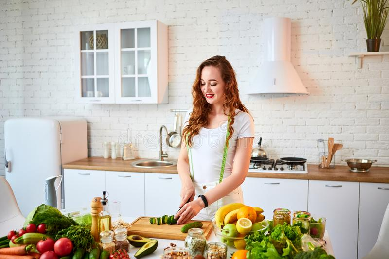 Young happy woman cutting cucumber for making salad in the beautiful kitchen with green fresh ingredients indoors. Healthy food royalty free stock photography