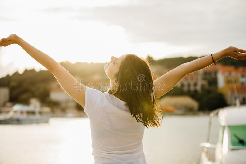 Young happy woman dancing under the sun.Happiness.Carefree female celebrating success.Romantic woman enjoying nature.Having fun. royalty free stock photos