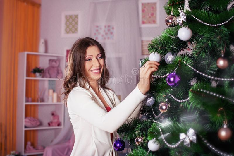 Young happy woman decorates a Christmas tree. The concept of the royalty free stock image