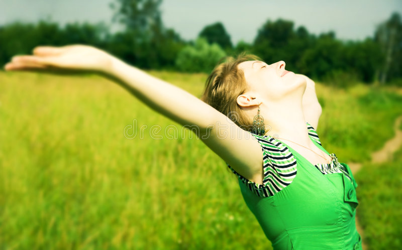 Young happy woman delighting good weather. Soft green tint stock photography