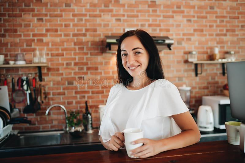 Young happy woman drinking coffee on the kitchen in the morning royalty free stock photo