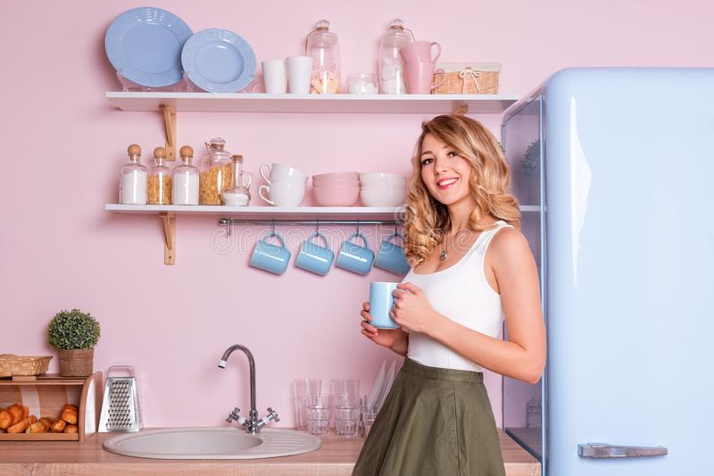 Young happy woman drinking coffee or tea at home in the kitchen. Blonde beautiful girl having her breakfast before going stock image