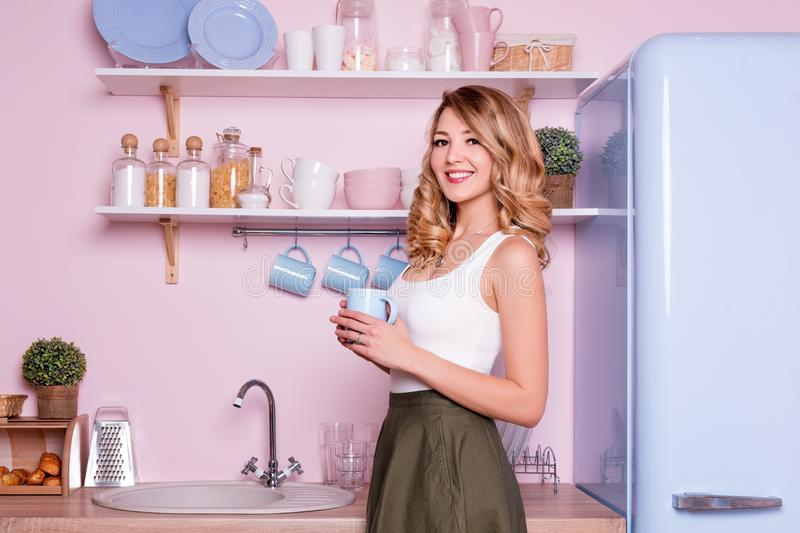 Young happy woman drinking coffee or tea at home in the kitchen. Blonde beautiful girl having her breakfast before going. To office. Coffee break. Pink and blue royalty free stock images