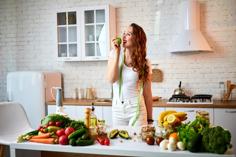 Young happy woman eating apple in the beautiful kitchen with green fresh ingredients indoors. Healthy food and Dieting concept. royalty free stock images
