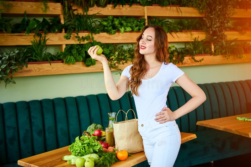 Young happy woman eating apple in the beautiful kitchen with green fresh ingredients indoors. Healthy food and Dieting concept. royalty free stock photography