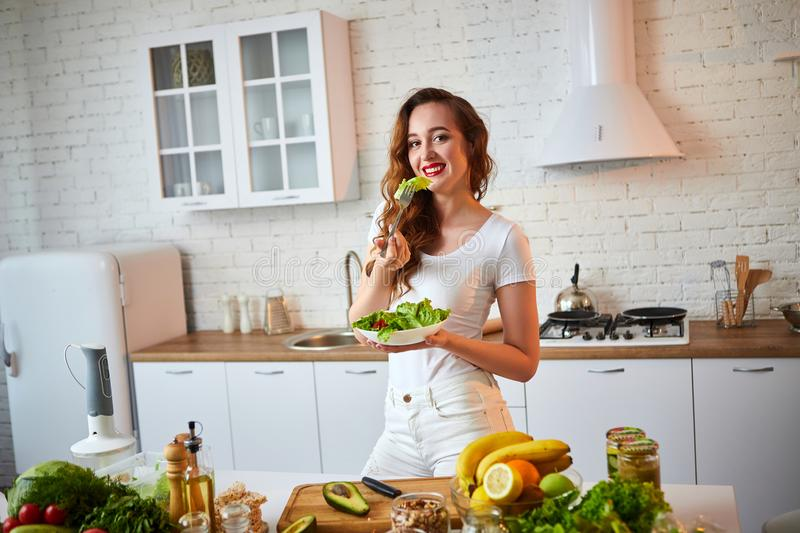 Young happy woman eating salad in the beautiful kitchen with green fresh ingredients indoors. Healthy food concept stock photo