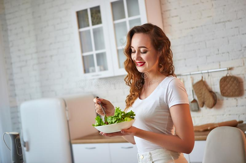 Young happy woman eating salad in the beautiful kitchen with green fresh ingredients indoors. Healthy food concept stock photography