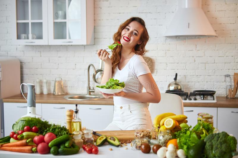Young happy woman eating salad in the beautiful kitchen with green fresh ingredients indoors. Healthy food concept stock image