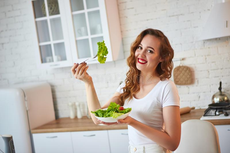 Young happy woman eating salad in the beautiful kitchen with green fresh ingredients indoors. Healthy food concept royalty free stock images