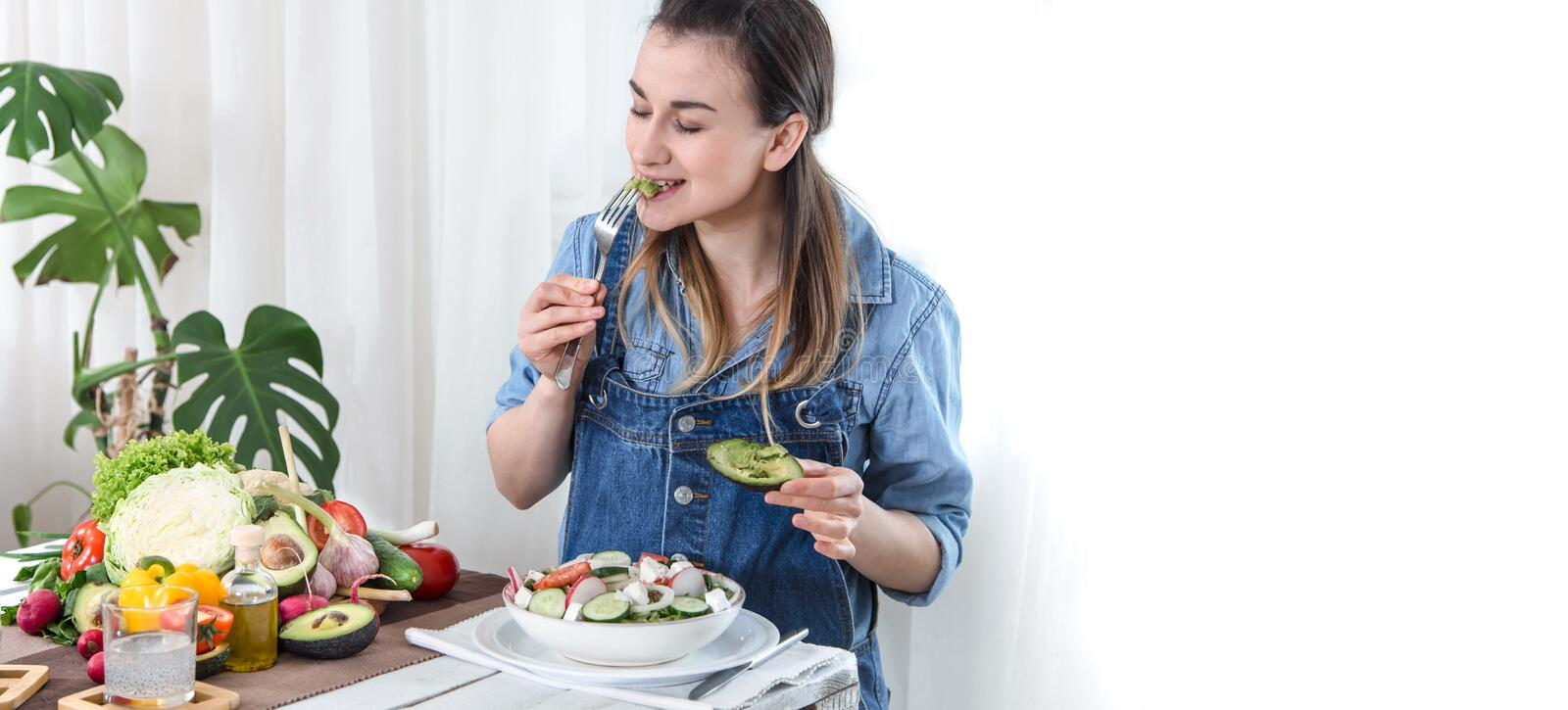 Young and happy woman eating salad at the table stock photos