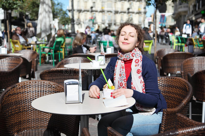 Young happy woman eats ice cream at outdoor cafe royalty free stock photos