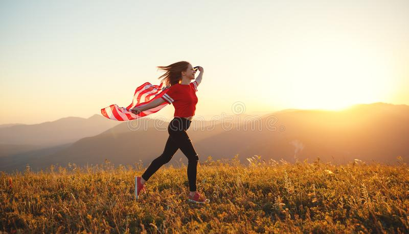 Happy woman with flag of united states enjoying the sunset on na. Young happy woman with flag of united states enjoying the sunset on nature royalty free stock photo