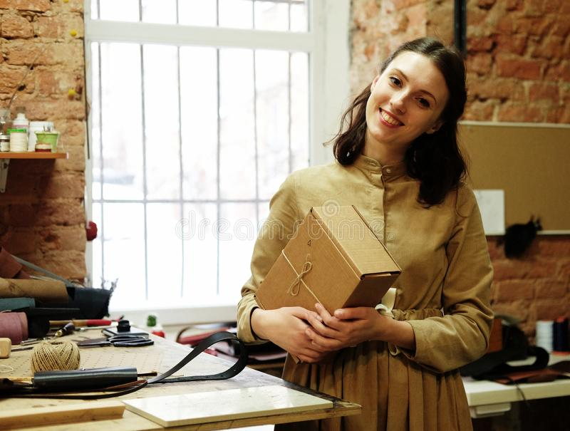 Young woman folds packing box in sewing workshop. Young happy woman folds packing box in sewing workshop royalty free stock photos