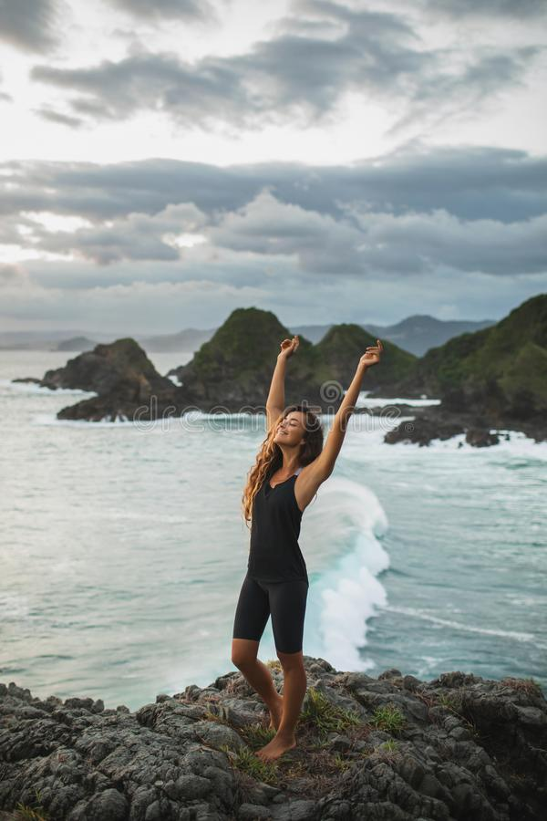Young happy woman hiking on hill with ocean view. Young happy woman on hill with ocean view. Goal achievement and happy well-being life concept stock photos