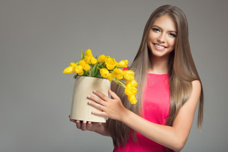 Young happy woman holding basket with yellow tulips. royalty free stock image