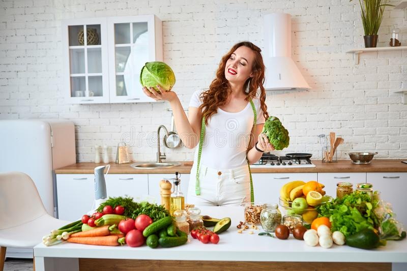 Young happy woman holding broccoli and cabbage in the beautiful kitchen with green fresh ingredients indoors. Healthy food and stock photos