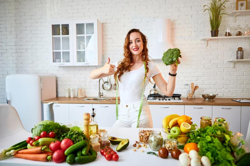 Young happy woman holding broccoli and showing thumbs up in the beautiful kitchen with green fresh ingredients indoors. Healthy stock photo