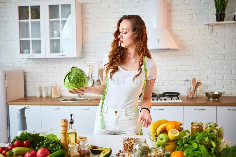 Young happy woman holding cabbage in the beautiful kitchen with green fresh ingredients indoors. Healthy food and Dieting concept royalty free stock photography