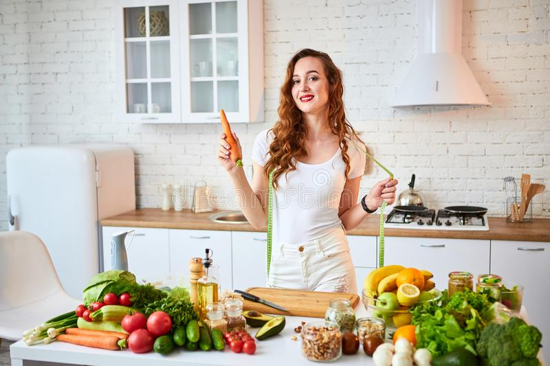Young happy woman holding carrot in the beautiful kitchen with green fresh ingredients indoors. Healthy food and Dieting concept. royalty free stock image