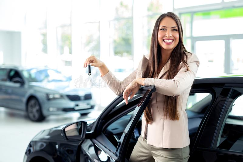 Happy woman holding keys to her new car at the dealership. Young Happy woman holding keys to her new car at the dealership royalty free stock images