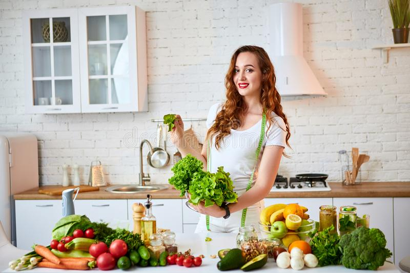Young happy woman holding lettuce leaves for making salad in the beautiful kitchen with green fresh ingredients indoors. Healthy royalty free stock photography