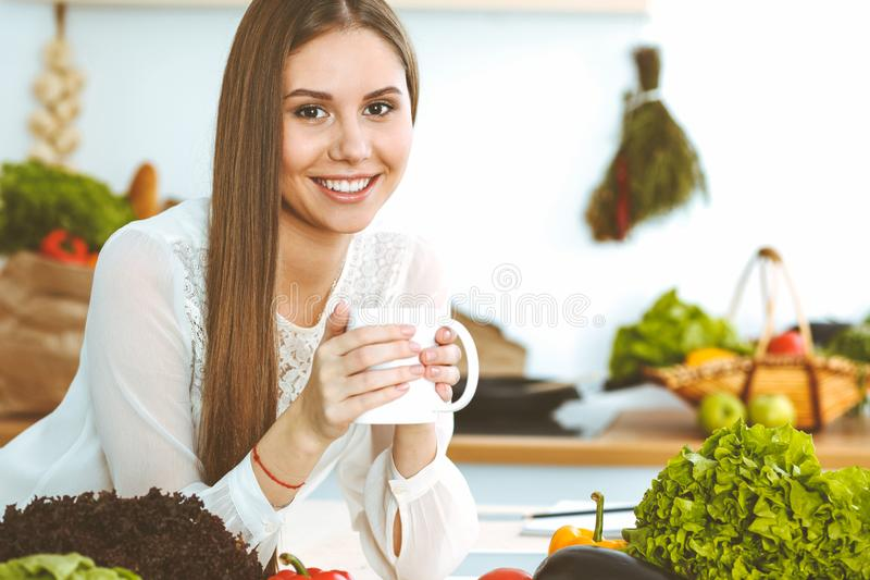 Young happy woman is holding white cup and looking at the camera while sitting at wooden table in the kitchen among. Young happy woman is holding white cup and royalty free stock images