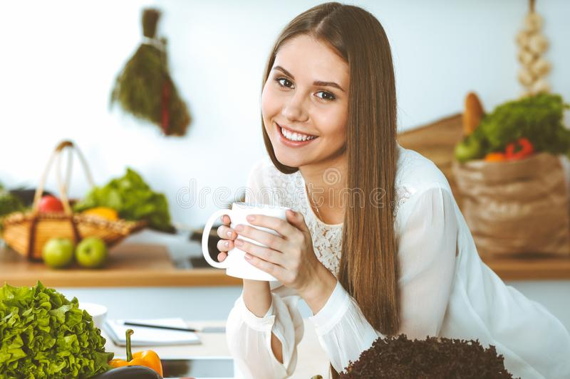 Young happy woman is holding white cup and looking at the camera while sitting at wooden table in the kitchen among. Young happy woman is holding white cup and royalty free stock photography