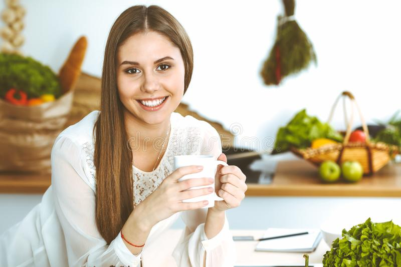 Young happy woman is holding white cup and looking at the camera while sitting at wooden table in the kitchen among. Young happy woman is holding white cup and stock images