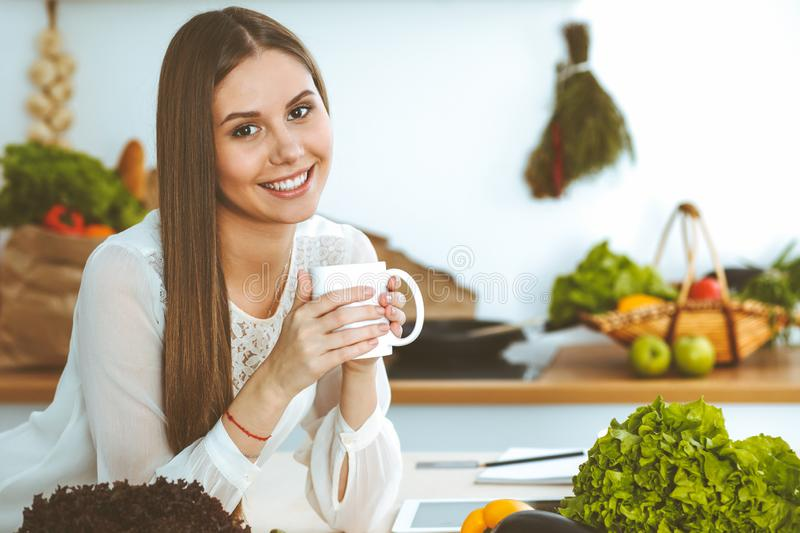 Young happy woman is holding white cup and looking at the camera while sitting at wooden table in the kitchen among royalty free stock photos