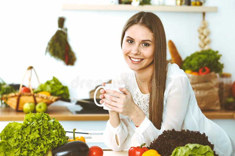 Young happy woman is holding white cup and looking at the camera while sitting at wooden table in the kitchen among royalty free stock photography