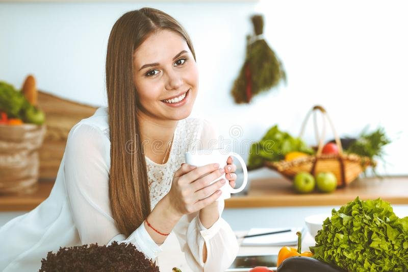 Young happy woman is holding white cup and looking at the camera while sitting at wooden table in the kitchen among. Young happy woman is holding white cup and stock photo