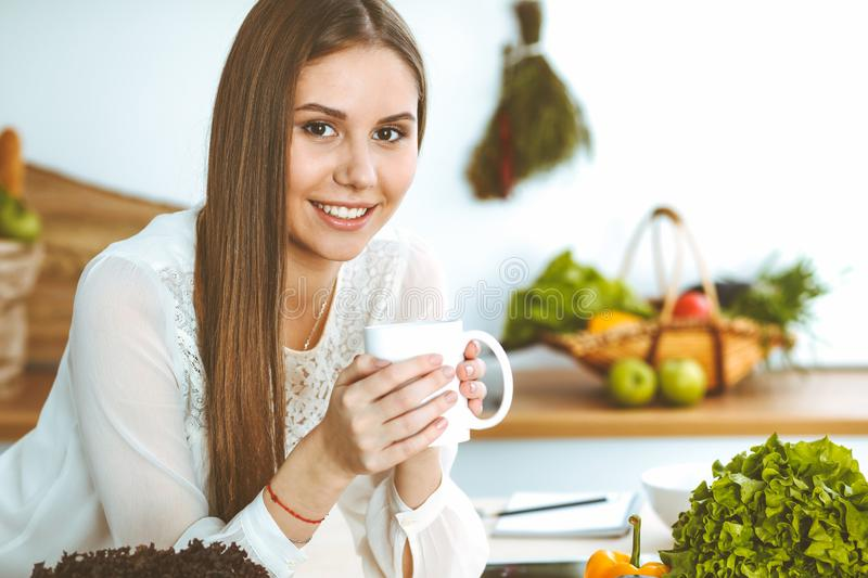 Young happy woman is holding white cup and looking at the camera while sitting at wooden table in the kitchen among. Young happy woman is holding white cup and royalty free stock photos